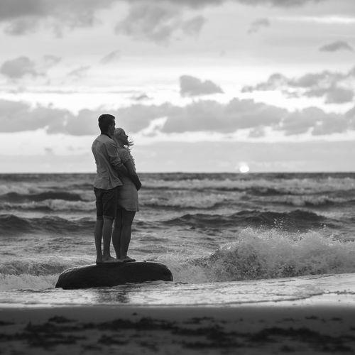 Full length of couple standing on beach against sky