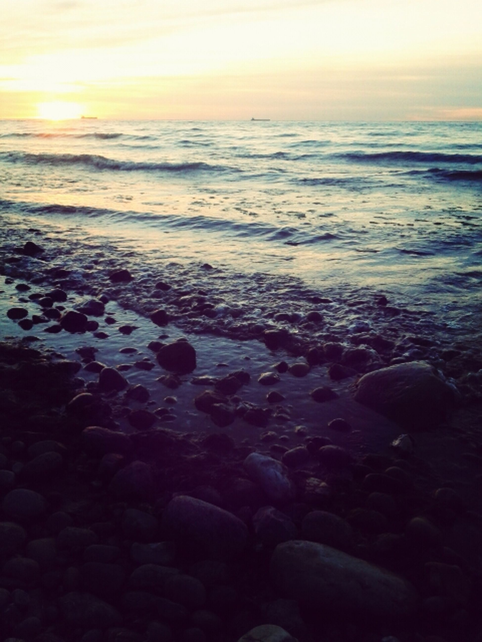 sea, beach, horizon over water, water, sunset, scenics, shore, beauty in nature, tranquil scene, tranquility, sun, nature, sky, idyllic, rock - object, wave, sunlight, stone - object, sand, outdoors