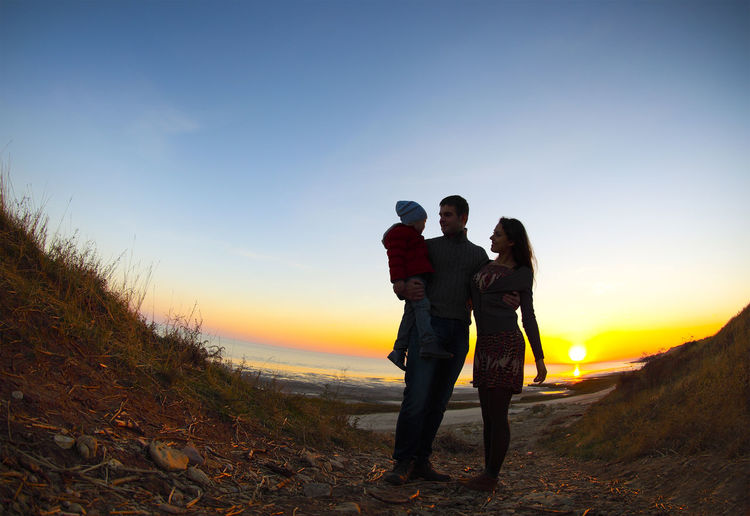 Couple standing on land against sky during sunset