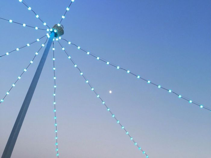 Low angle view of fairy lights against clear blue sky