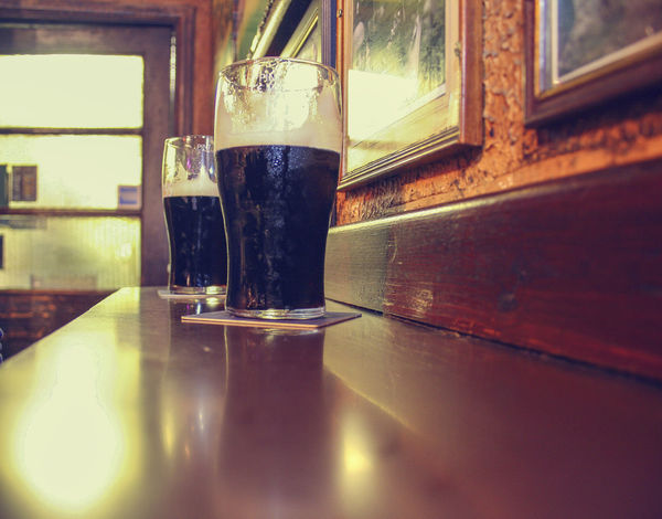 Two glasses of famous black Irish stout in Irish pub on wooden bar Alcohol Ale Bar Barley Beer, Beverage Black Close-up Copy Space Counter Drinks Dublin Famous Glass Guiness Half A Pint Ireland Irish Pint Pub Stout Two