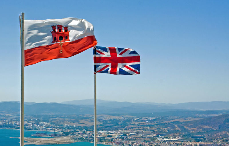 Union Jack flying with the flag of Gibraltar on top of The Rock of Gibraltar Blue British Flag Clear Sky Cultur Flag Flag Pole Flags Gibraltar Gibraltar Flag Gibraltar Is British Identity Landscape National Flag Outdoors Patriotism Pole Red, White And Blue Two Flags Union Flag Union Jack Union Jack Flag View Wind