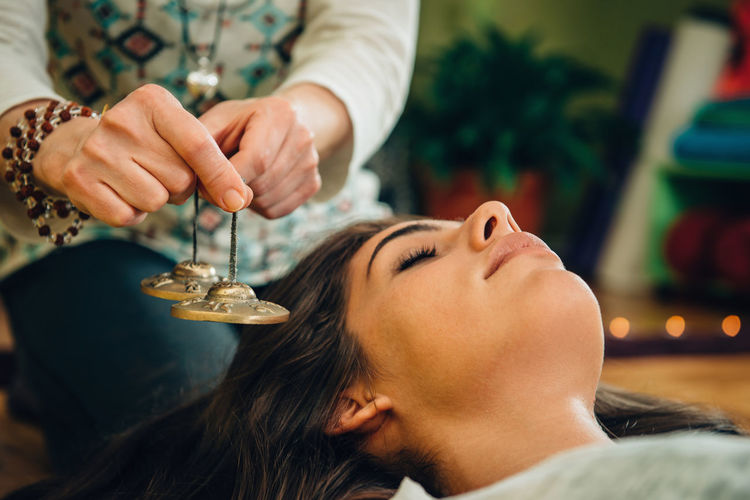 Midsection Of Therapist Holding Bells By Young Woman At Spa
