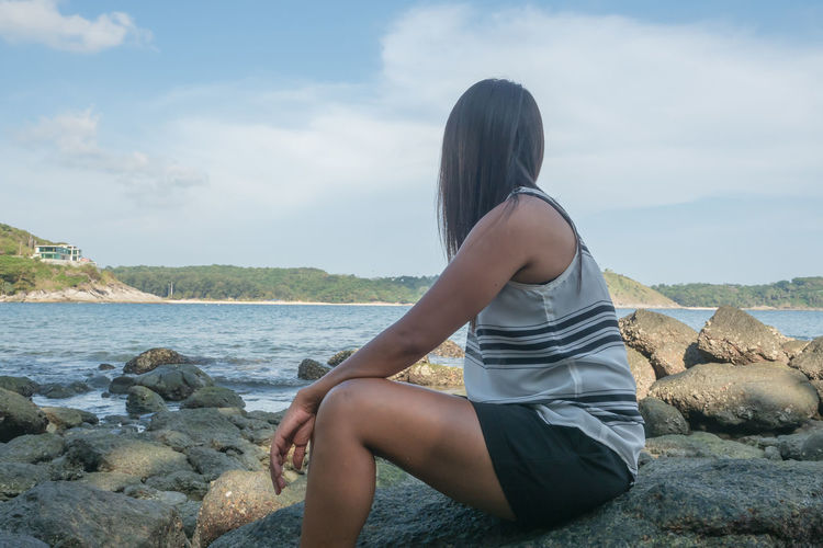 Side view of young woman sitting on rock by sea against sky