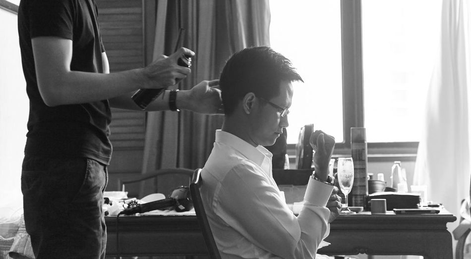 Midsection of male hairdresser spraying on bridegroom hair during wedding
