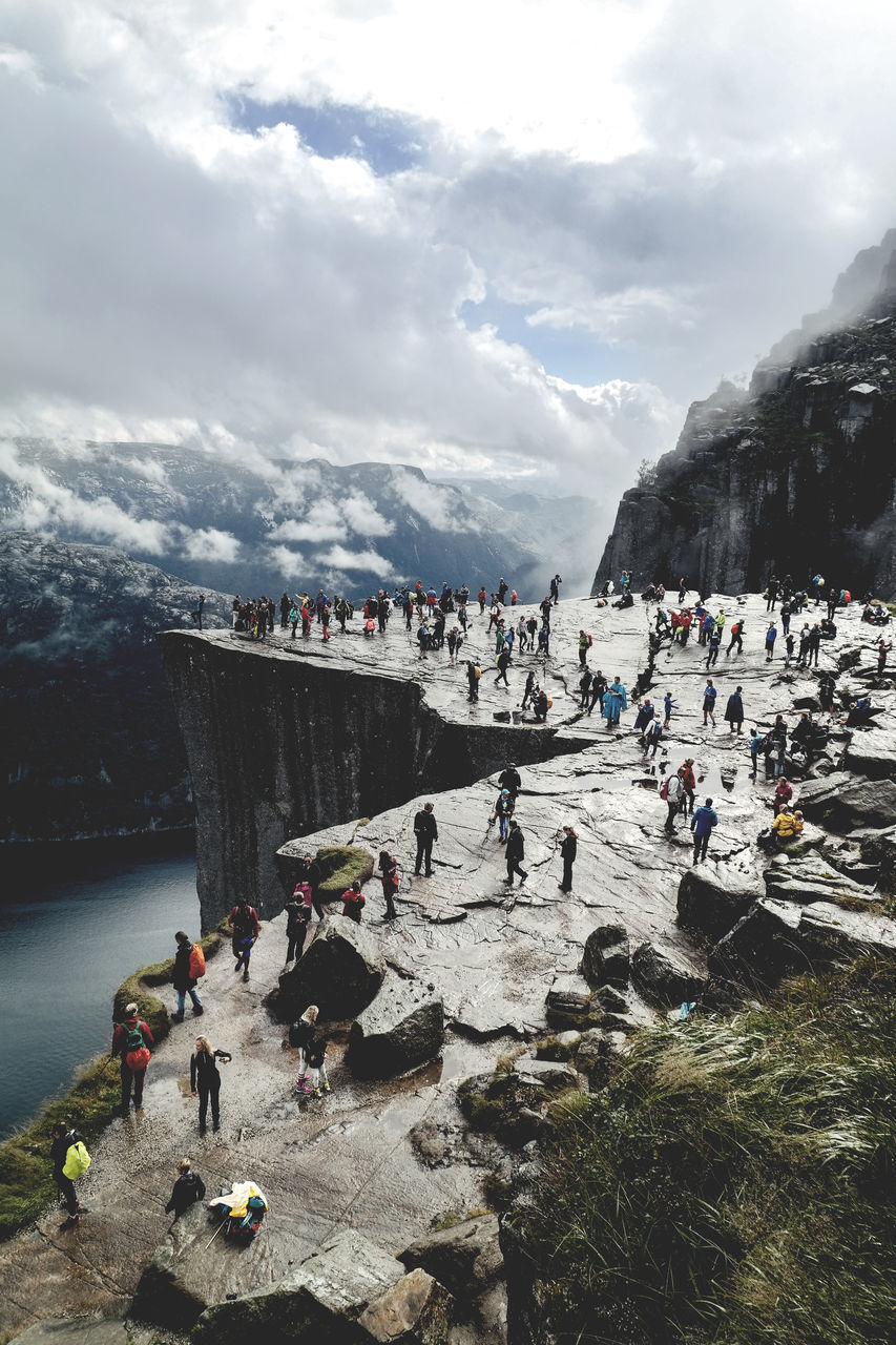 High Angle View Of People On Mountain Against Cloudy Sky During Winter