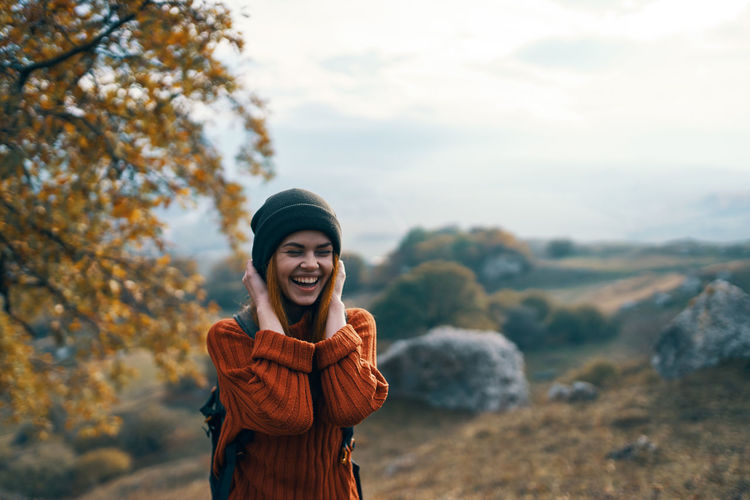 Smiling young woman standing outdoors during autumn against sky