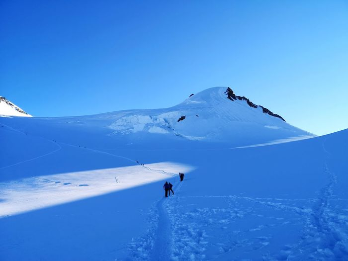People on snowcapped mountain against blue sky