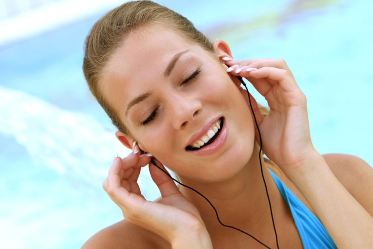 young blond woman listening to music with MP3 players at the pool Beautiful Happy Holiday Listening Music Music Summer Holidays Woman Beautiful Woman Bikini Blond Close-up Girl Happyness Headshot Leisure Leisure Activity Lifestyles Mp3 Player People Pretty Relaxation Swimming Pool Vacation Water Wellbeing