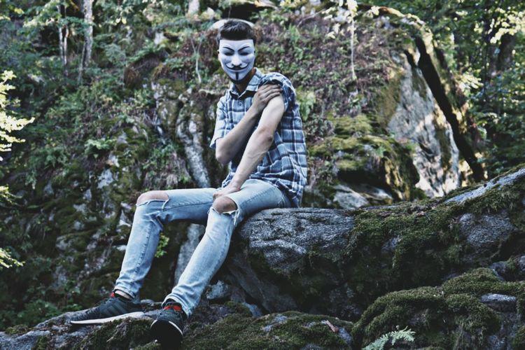 Full length of man wearing mask sitting on rock