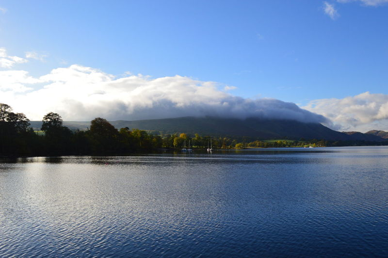 Scenic view of lake with clouds over mountains against sky
