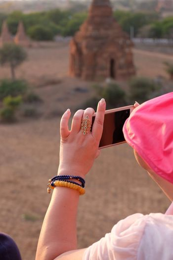 Close-up rear view of a woman photographing with mobile phone