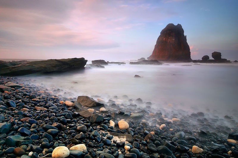 Scenic view of Papuma Beach, Indonesia. Sunrise or sunset view with wave motion. Soft focus effect due to slow shutter speed. Small black rocks at the beach and big rock middle of the sea as background. Rock Wave Beach Beauty In Nature Black Rock Blue Day Island Landscape Nature No People Outdoors Pebble Pebble Beach Refreshing Rock - Object Scenics Sea Shore Sky Splashing Sunset Tranquil Scene Tranquility Water