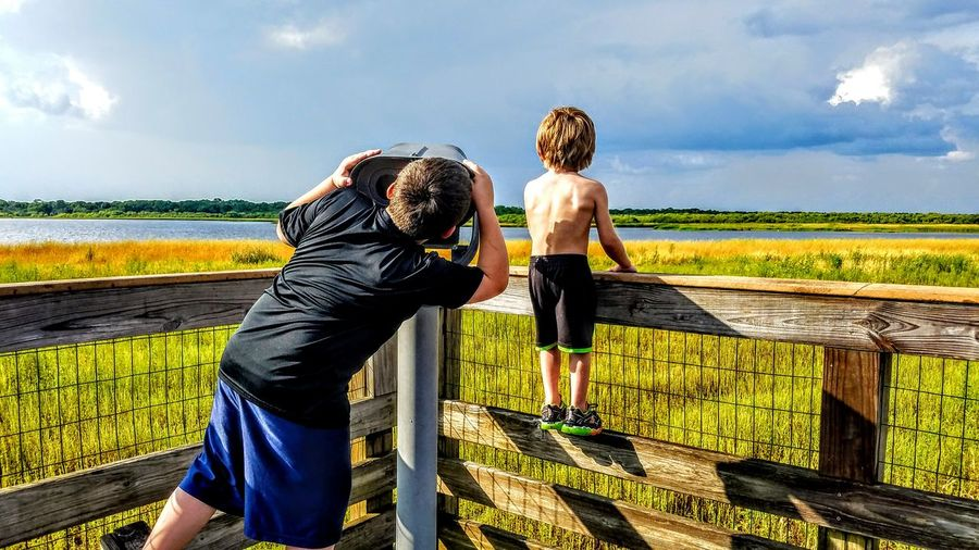 Rear view of boy looking in coin-operated binoculars by brother on fence against sky