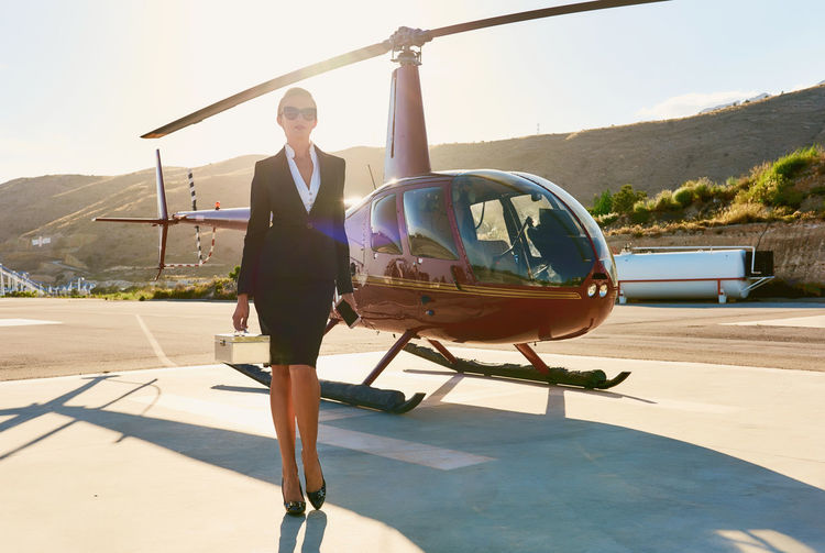 Businesswoman wearing sunglasses standing by helicopter during sunny day