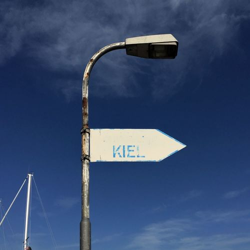 Low Angle View Of Arrow Symbol With Text On Street Light Against Blue Sky