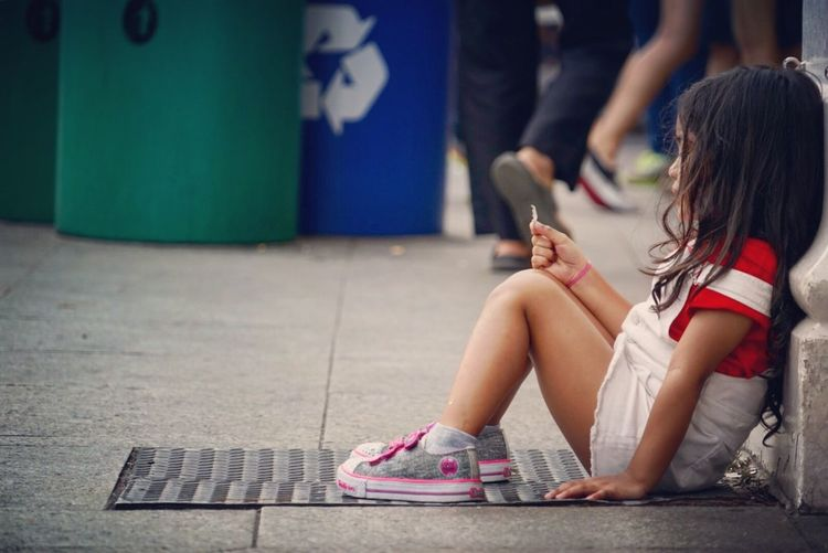 Low section of girl sitting on mobile phone