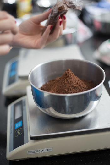 Cropped image of woman weighing coffee powder in store