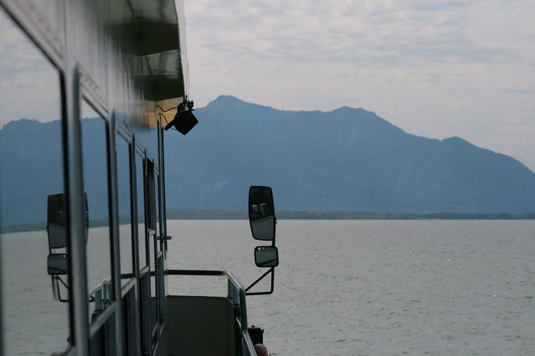 Cropped image of boat sailing on lake against mountains