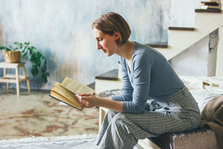 Side view of young woman sitting on book