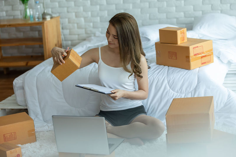 Full length of young woman using laptop while sitting by bed at home