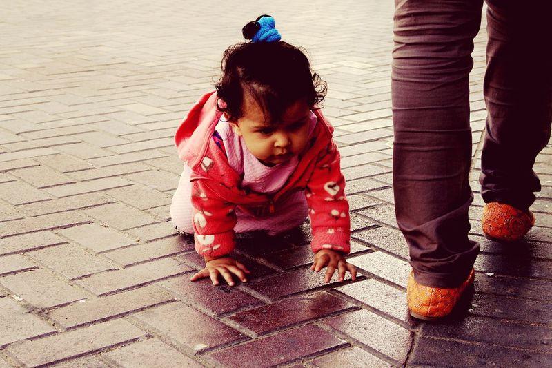 Cute baby girl crawling on footpath