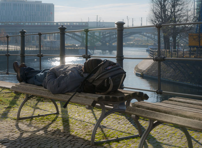 Adult Adults Only Alone Architecture Bench City Day Laying Down Lonely Lonely Person One Man Only One Person Outdoors People Reflection River Seating Bench Sitting Sky Sleeping Sunny Water Capture Berlin