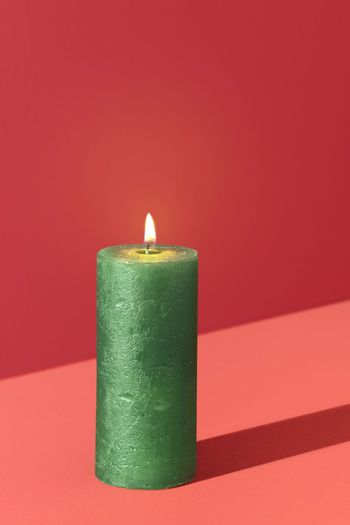 Close-up of lit candle against red background