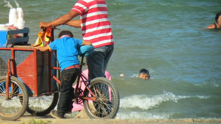 Two People Outdoors Water Leisure Activity Cycling Togetherness Men Vacations Real People Adult Day People Adults Only Low Section Child Work Child Worker Helping Beach Coast Job Slpash The Photojournalist - 2017 EyeEm Awards Live For The Story