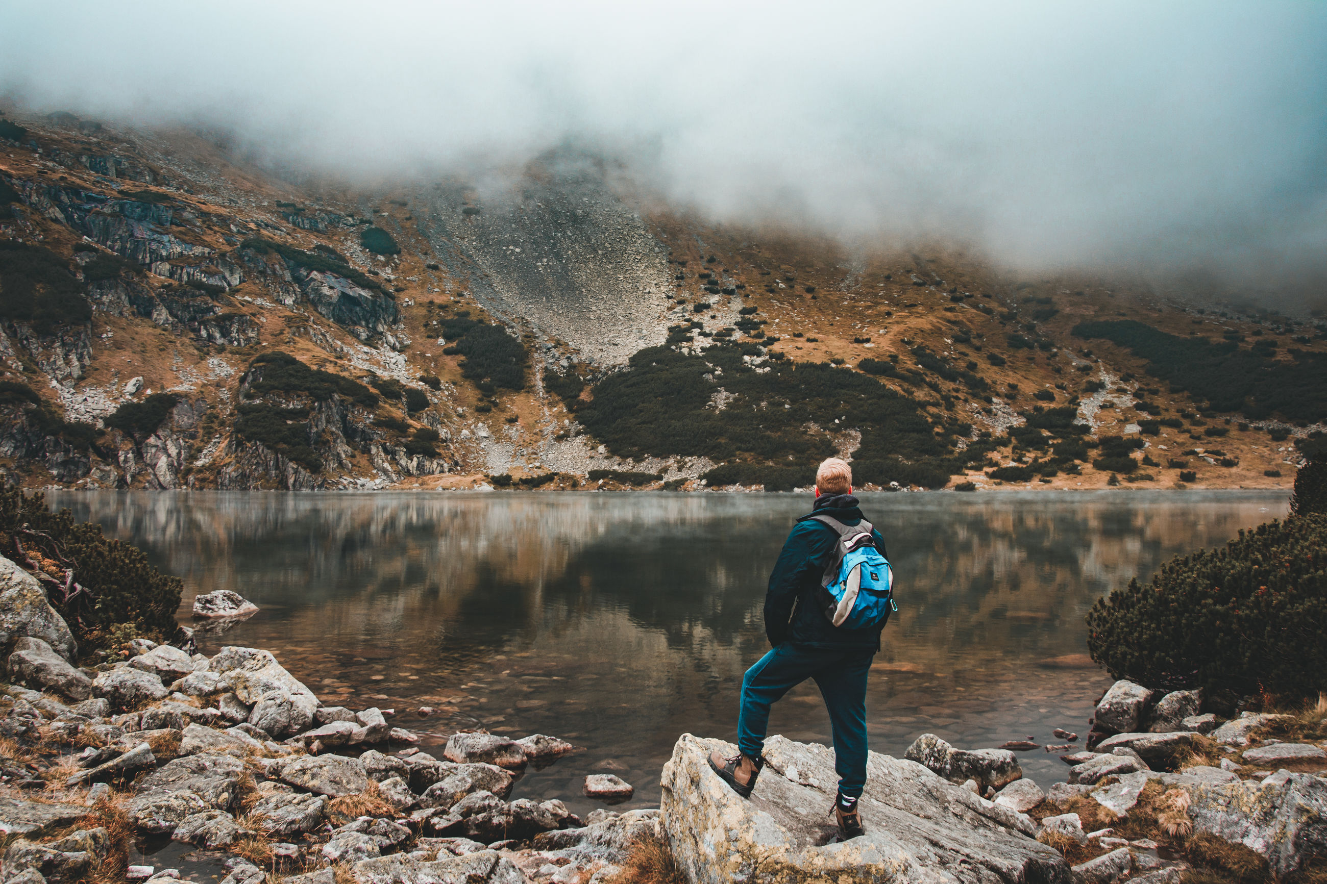 water, full length, rock, one person, beauty in nature, real people, rock - object, scenics - nature, solid, non-urban scene, lifestyles, mountain, leisure activity, standing, nature, tranquility, lake, casual clothing, tranquil scene, outdoors