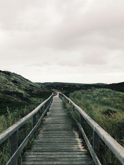View of wooden boardwalk leading towards landscape against sky