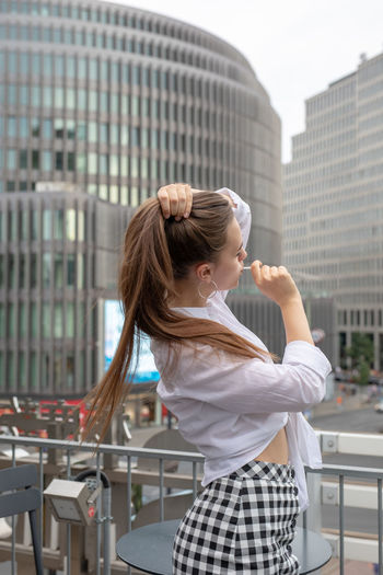 Young woman eating lollipop while standing by buildings in city