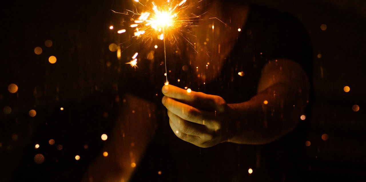 Midsection of man holding sparkler at night