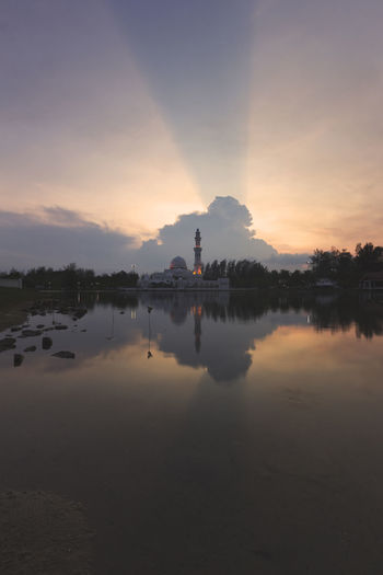 Rays of light was captured during sunset at a mosque. Architecture Architecture, Mosque, Religion, Islam, Asia, East, Famous, Minaret, Muslim, Dome, Landmark, Islamic, Sunset, Travel, Sky, Arabic, Religious, Dusk, Building, Evening, Ramadan, Marble, Culture, Grand, Reflection, Nature, Sunrise, Belief, Stone, Pillars, Pat Beauty In Nature Building Exterior Built Structure Day Lake Nature No People Outdoors Reflection Scenics Silhouette Sky Sunset Tranquil Scene Tranquility Tree Water Waterfront