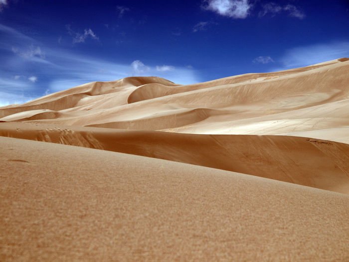 Desert Nature Sky Landscape Day Outdoors Tranquility Sand Sand Dunes Isolation Scenics Beauty In Nature No People Shapes And Patterns  Sand Dune Shapes In Nature  Tranquil Scene Low Angle View Non-urban Scene Cloud - Sky Arid Climate Extreme Terrain Physical Geography
