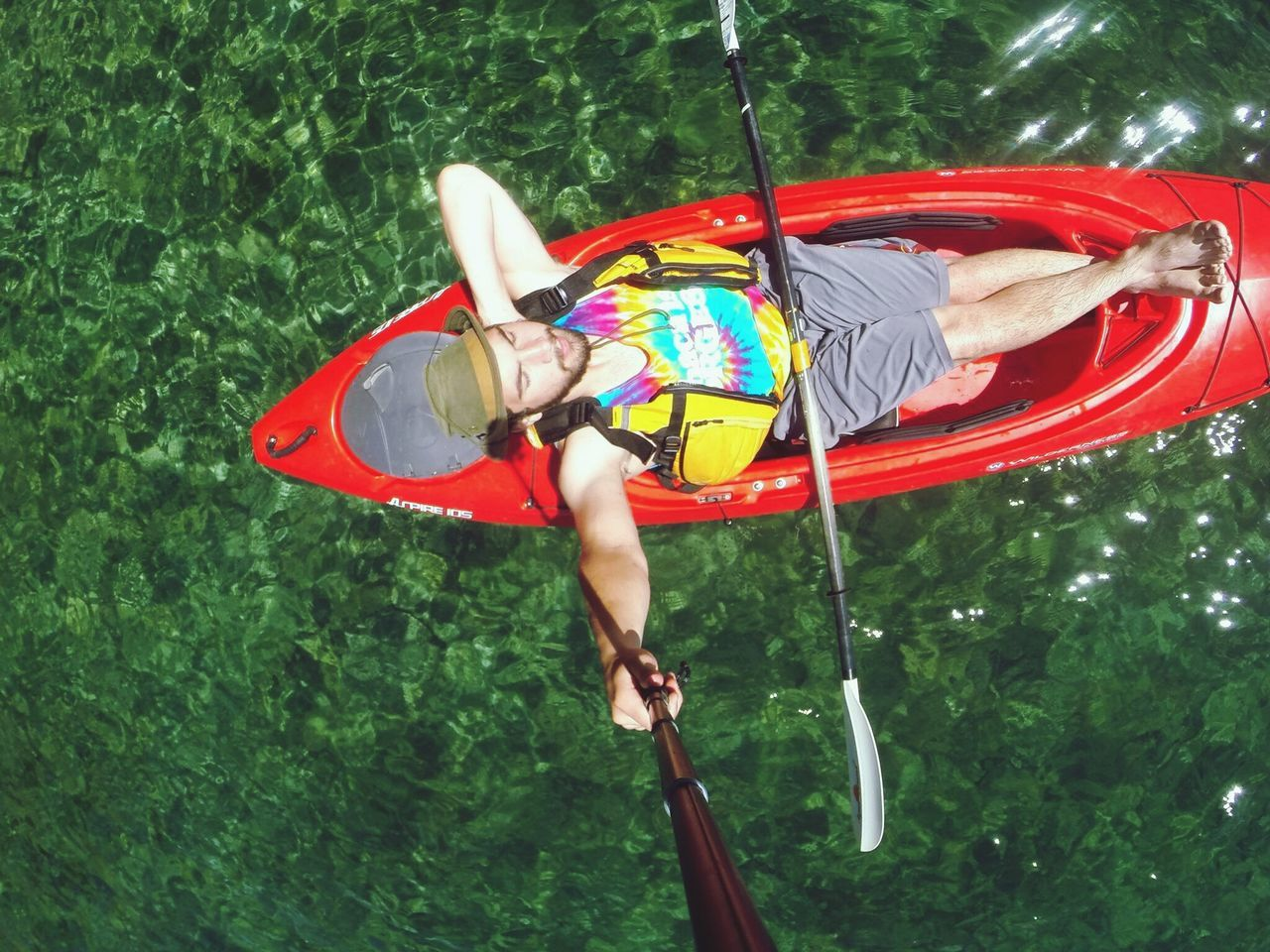 High angle view of young man relaxing on kayak in lake
