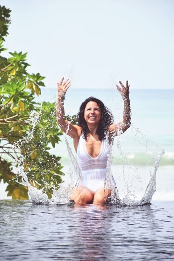 Happy young woman playing with water while sitting in infinity pool