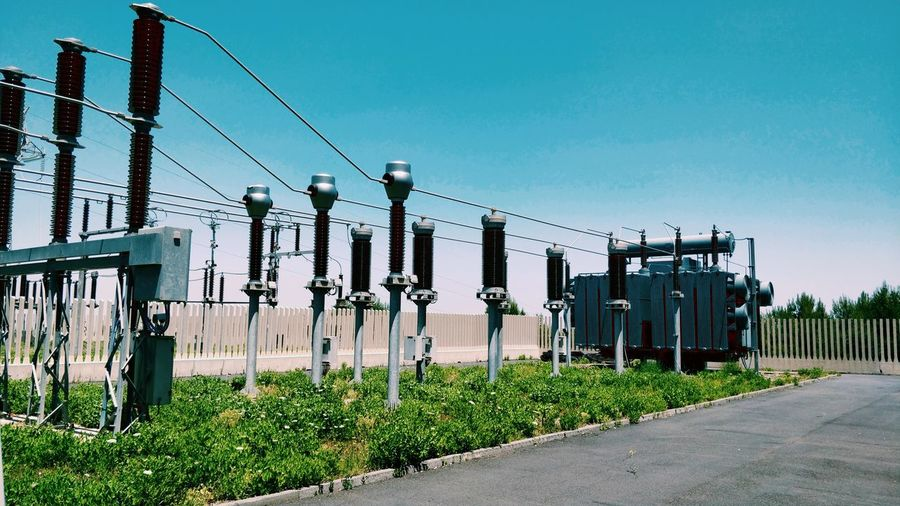 Transformers at substation against clear blue sky