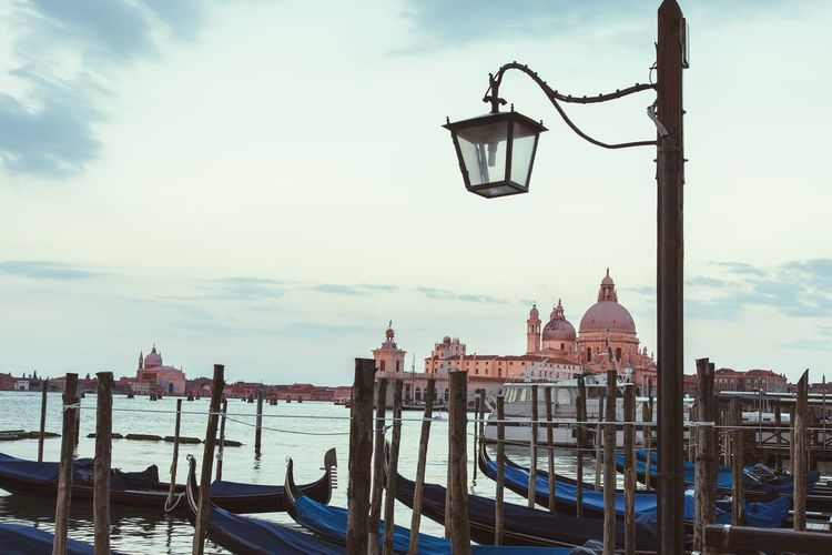 Street lamp by gondolas on grand canal against sky