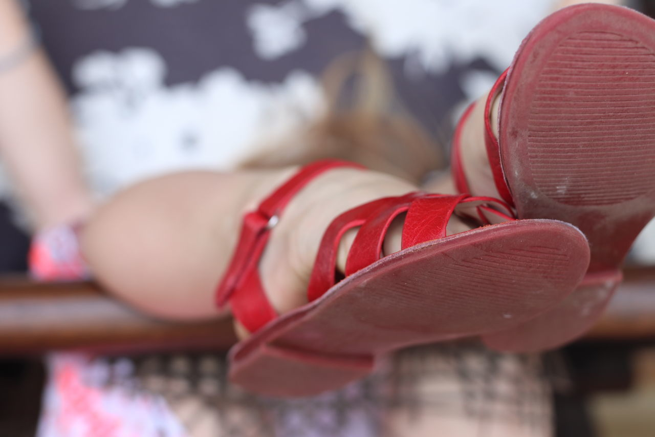 CLOSE-UP OF WOMAN WITH RED SHOES