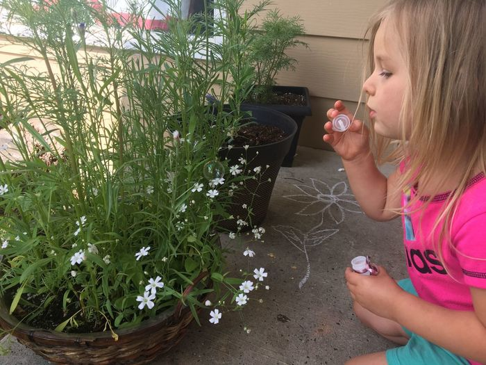 Side view of girl blowing bubbles by flowering plants on porch