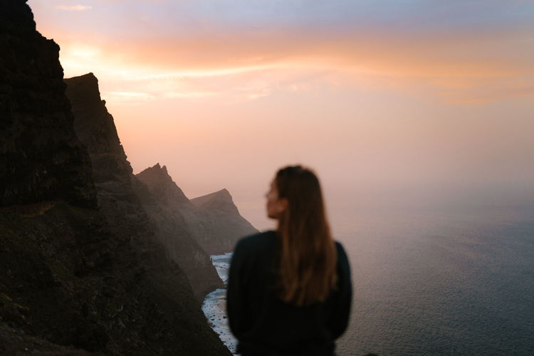 Girl out of focus looking away in front of big cliffs