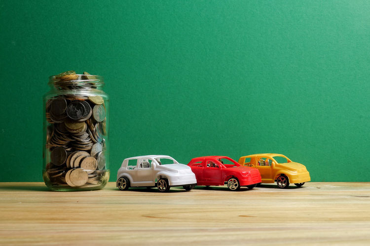 Auto Car Colored Background Container Copy Space Finance Financing Green Background Green Color Indoors  Jar Large Group Of Objects No People Plastic Saving Savings Still Life Studio Shot Table Toy Toy Car Wood - Material