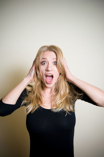 Young blonde woman expression portrait Amazed Astonished Blond Hair Crying Front View Indoors  Long Hair Looking At Camera Mouth Open One Person People Portrait Studio Shot Surprised Woman Young Young Adult