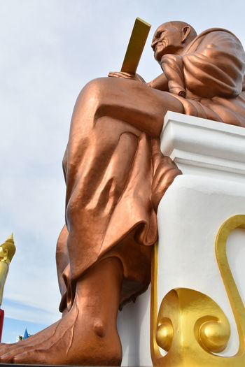 Low angle view of somdej toh statue at wat bot temple against sky