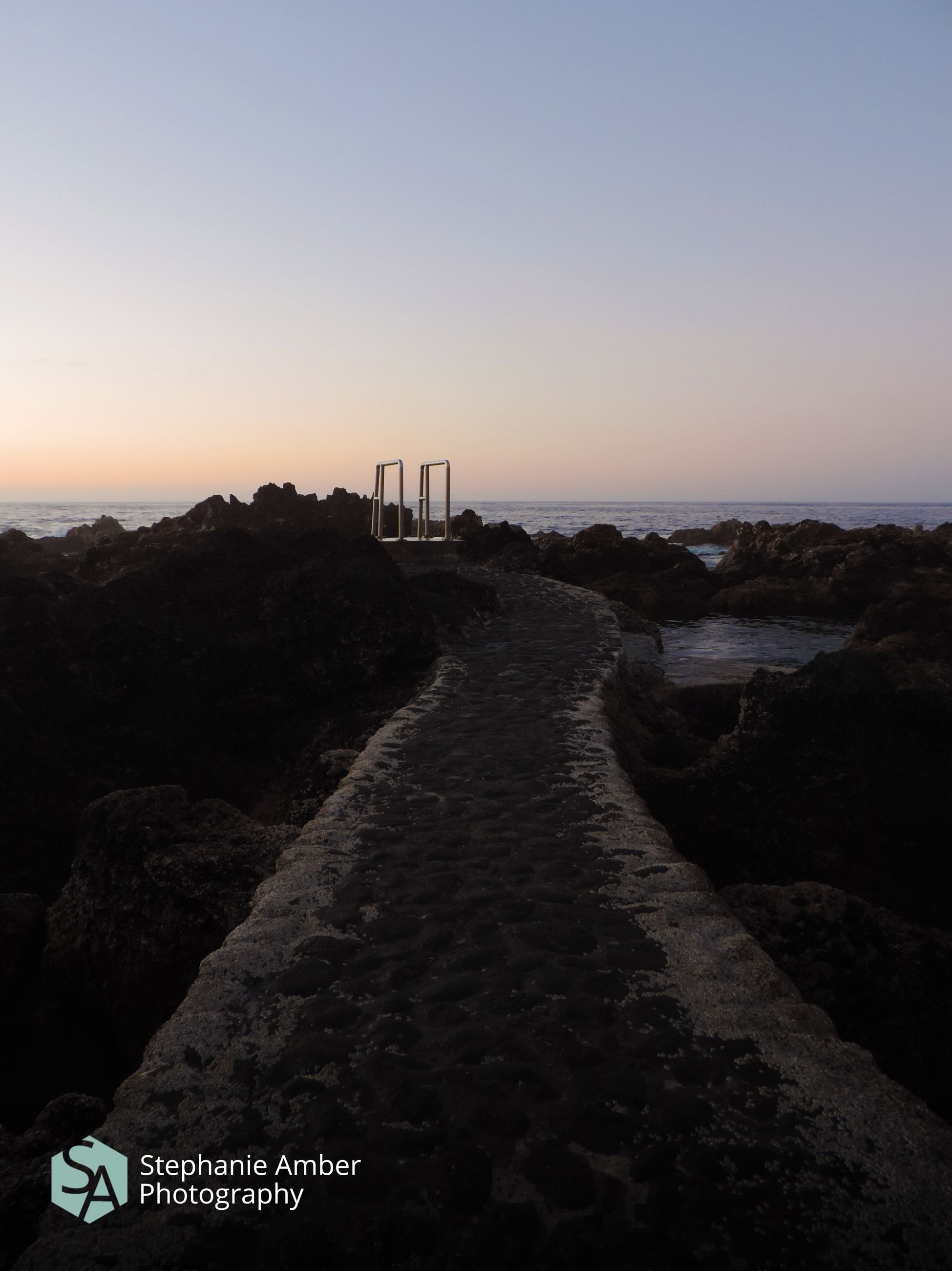 sky, sunset, scenics - nature, sea, nature, beauty in nature, water, architecture, direction, tranquil scene, built structure, copy space, no people, tranquility, text, the way forward, clear sky, rock, building exterior, horizon over water