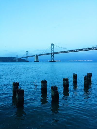 Wooden posts on river with oakland bay bridge in background against sky