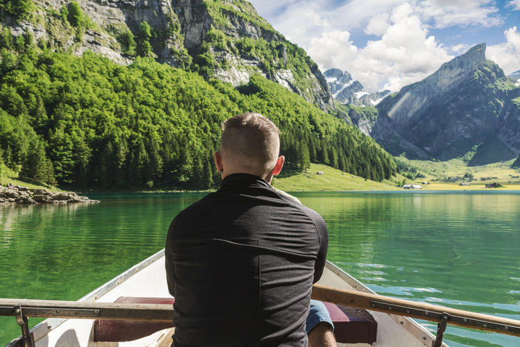 Rear View Of Man Rowing Boat In Lake Against Mountains