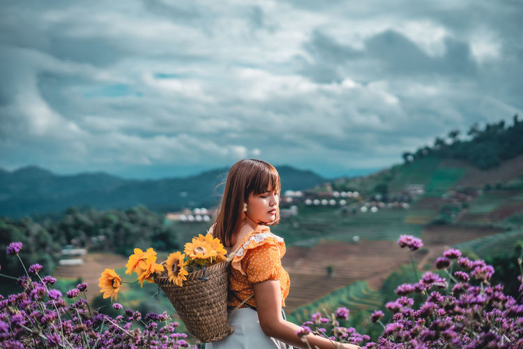 Woman amidst yellow flowering plants