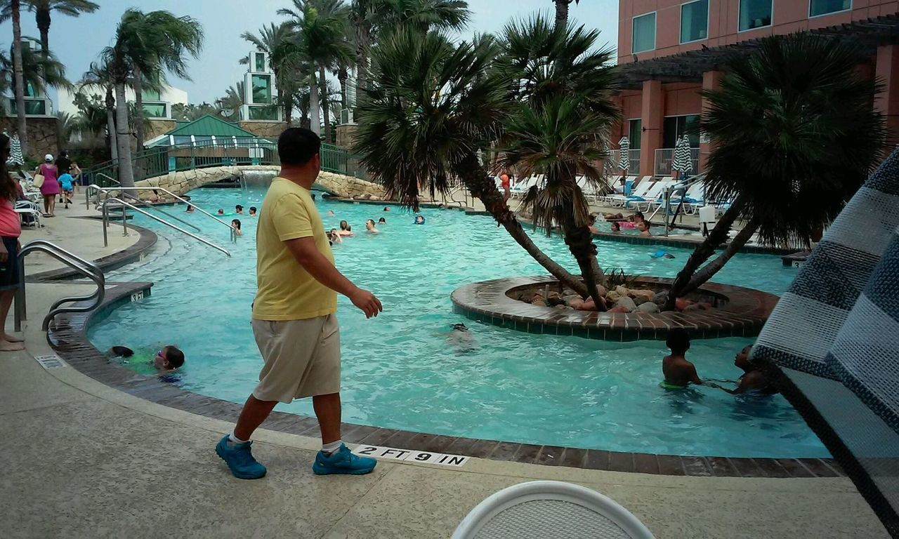 swimming pool, palm tree, water, real people, tree, built structure, building exterior, men, outdoors, lifestyles, architecture, vacations, leisure activity, tourist resort, full length, one person, day, standing, water park, sea, city, nature, sky, people, adult